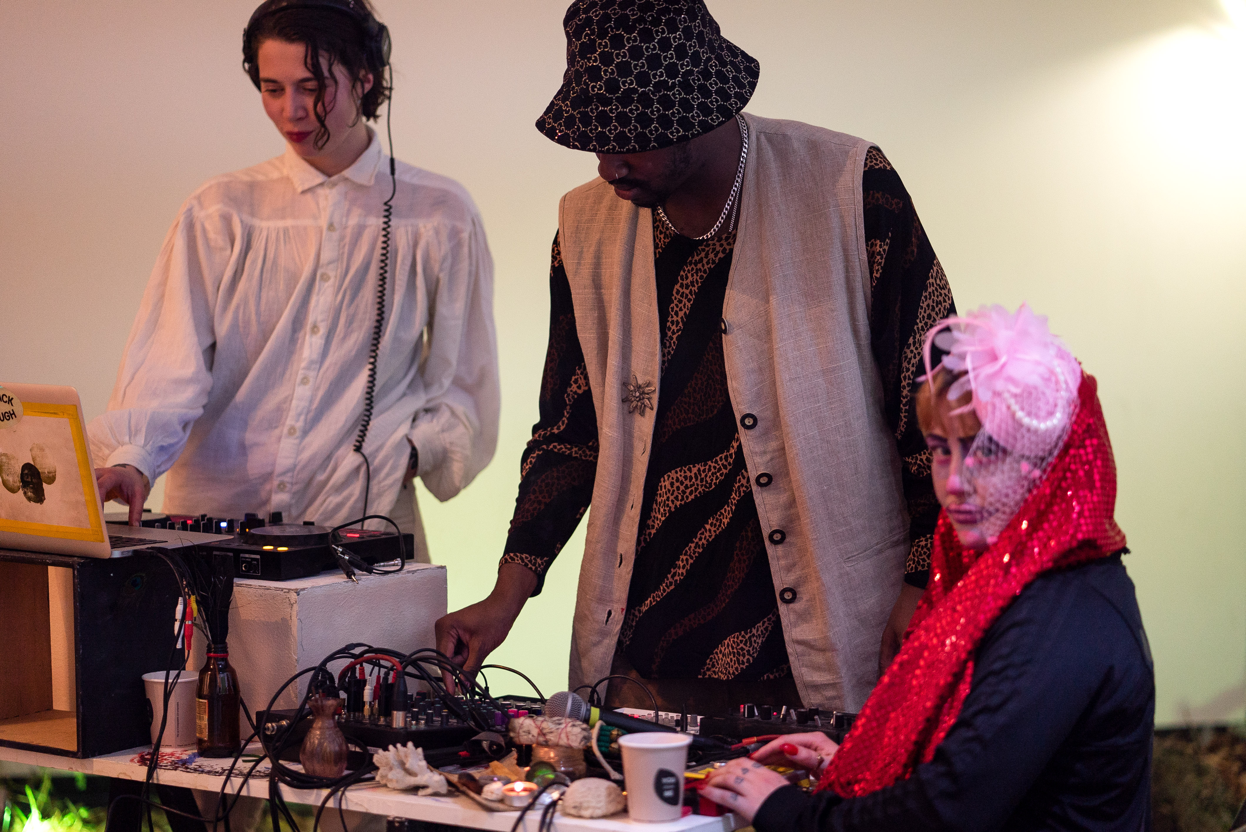 The photo is a medium shot of three people around a DJ table. The person on the far left is wearing white clothes, headphones and has one hand on a laptop. The person in the middle wears a hat, a traditional vest and operates DJ equipment. The person on the far right is the only one sitting at the table and looking towards the camera. She is wearing a large pink flower on her head and has a glittering red scarf wrapped around her neck.