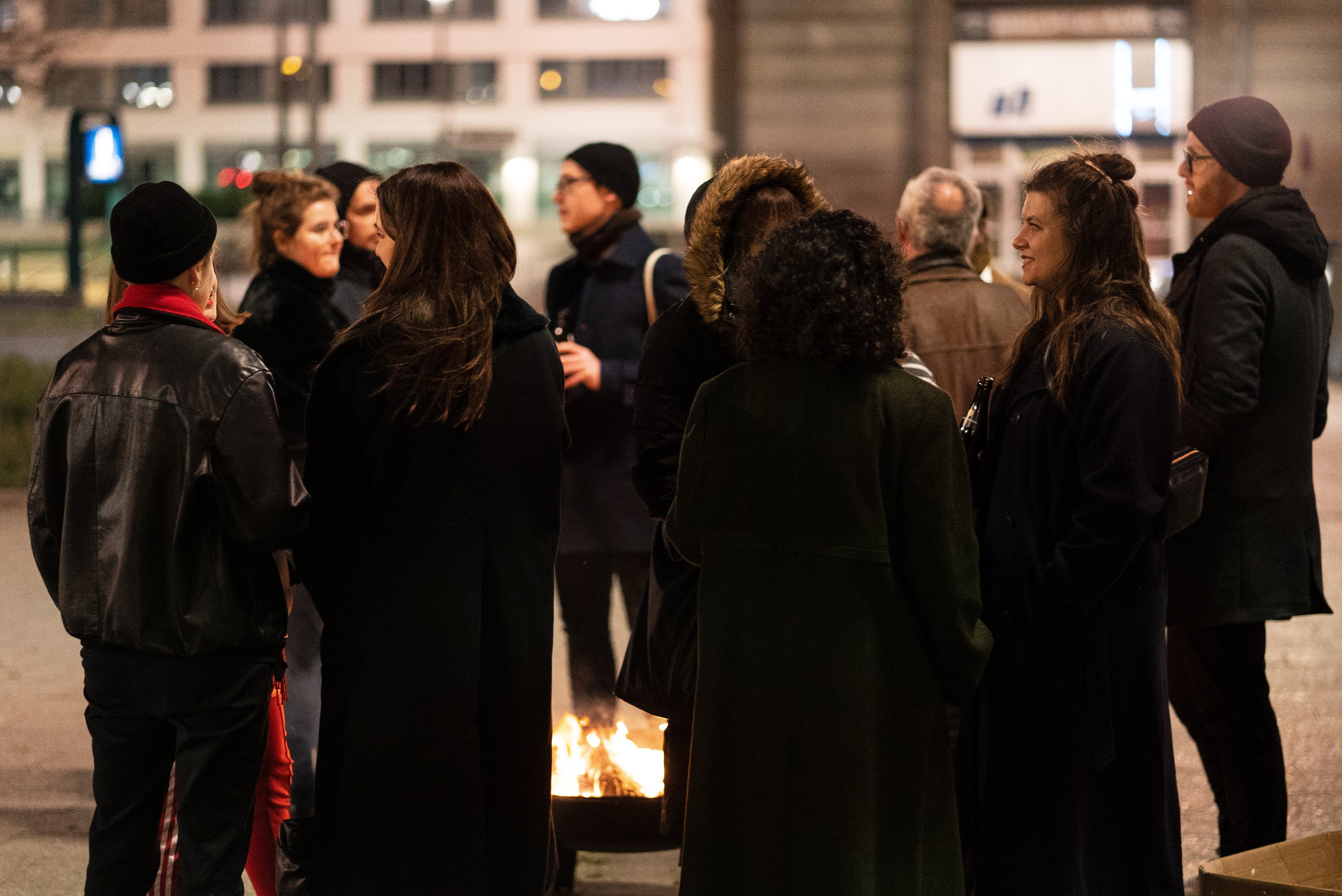 The photo shows several people standing around a fire in the evening in an urban area and talking.