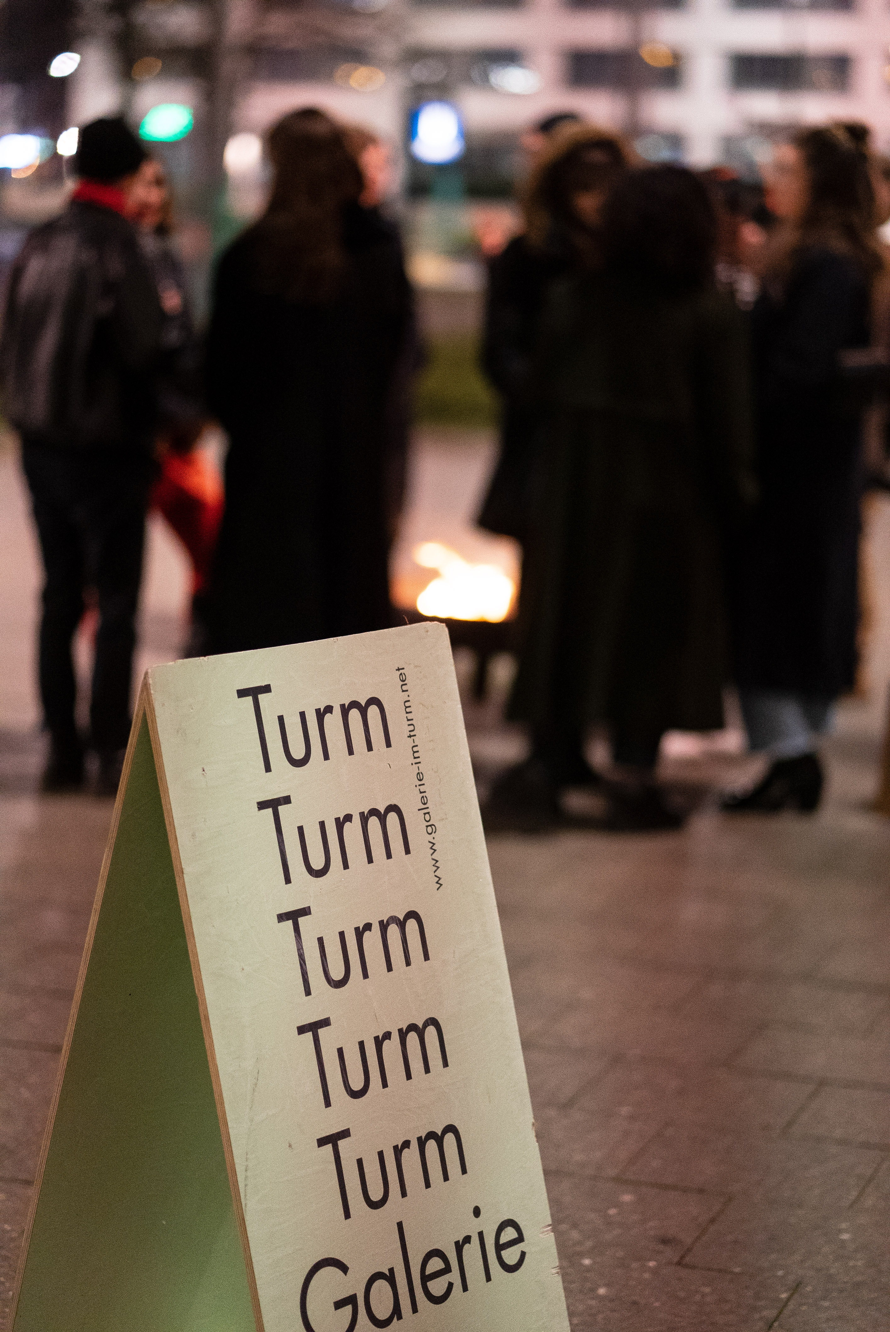 The photo shows in the foreground a sandwich-board sign for the exhibition location, Galerie im Turm. It is evening. In the background in the blur, people stand around a fire bowl.