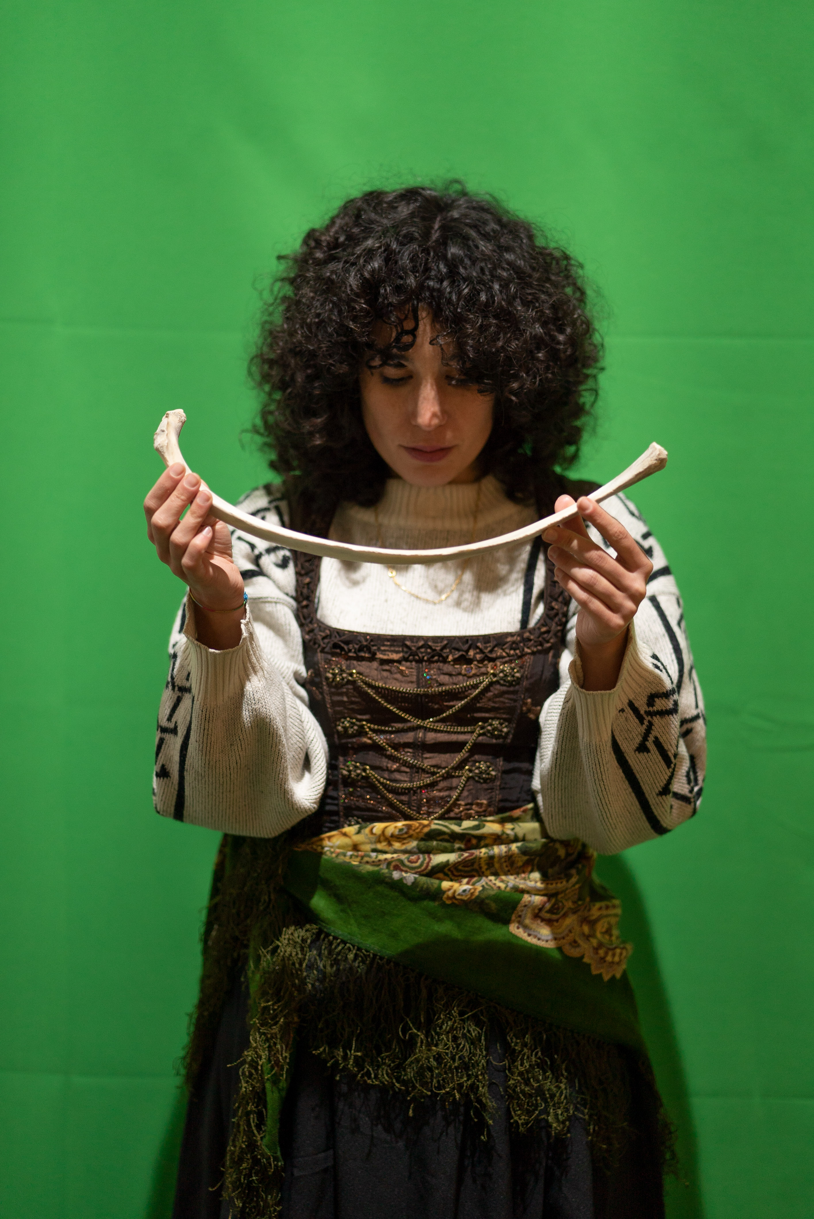 The photo is a medium shot of a person in front of a green screen. They have black curls, wear a wool sweater and over it a traditional costume dress with a scarf around their hips. With their hands they hold a 40cm long bone in front of their face. Their head is lowered and their eyes are directed to the ground.