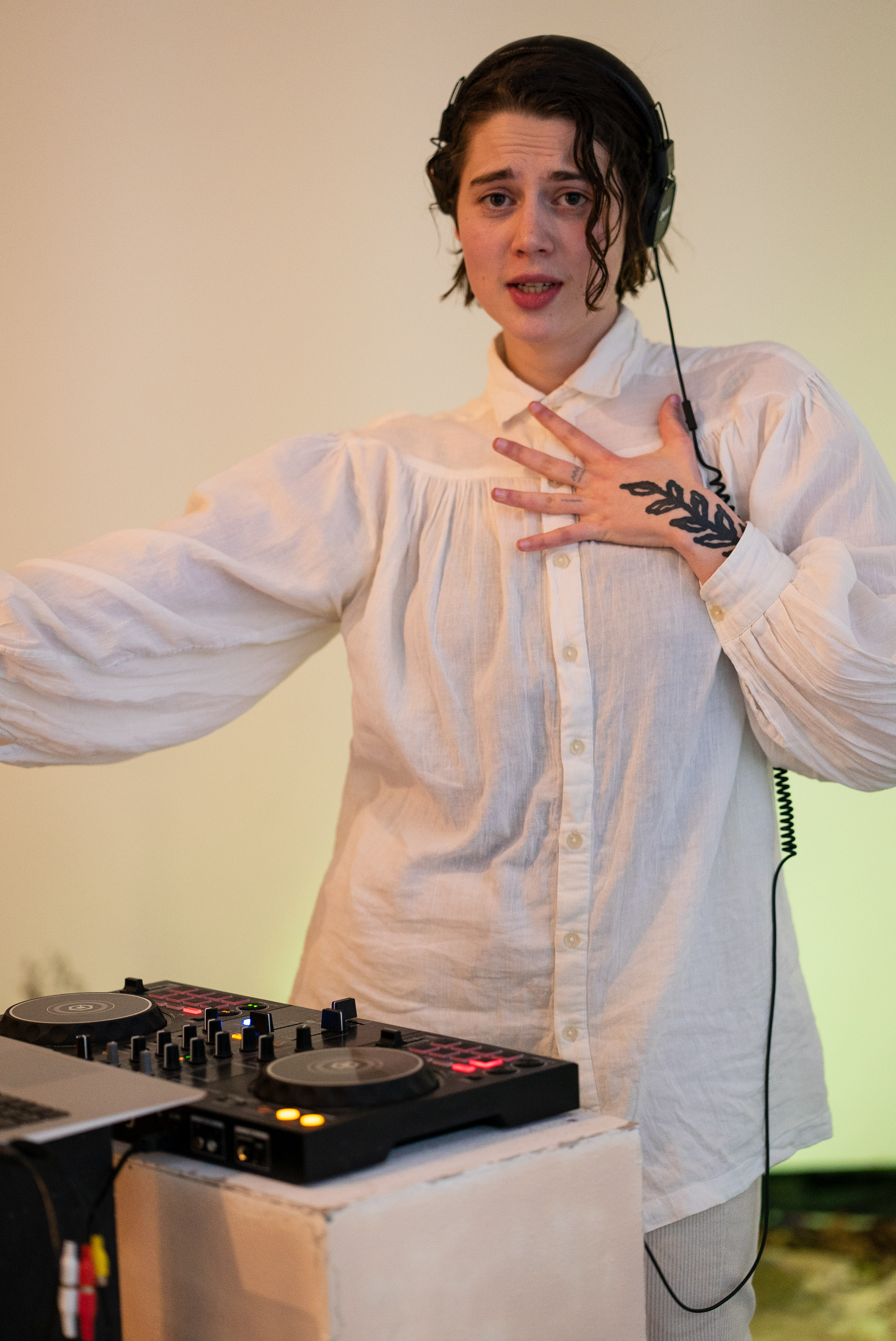 The photo is a medium shot of a person wearing white clothes and headphones dancing in front of a dj table. With the left hand on their chest they are looking into the camera, their mouth looks like as if they were singing.