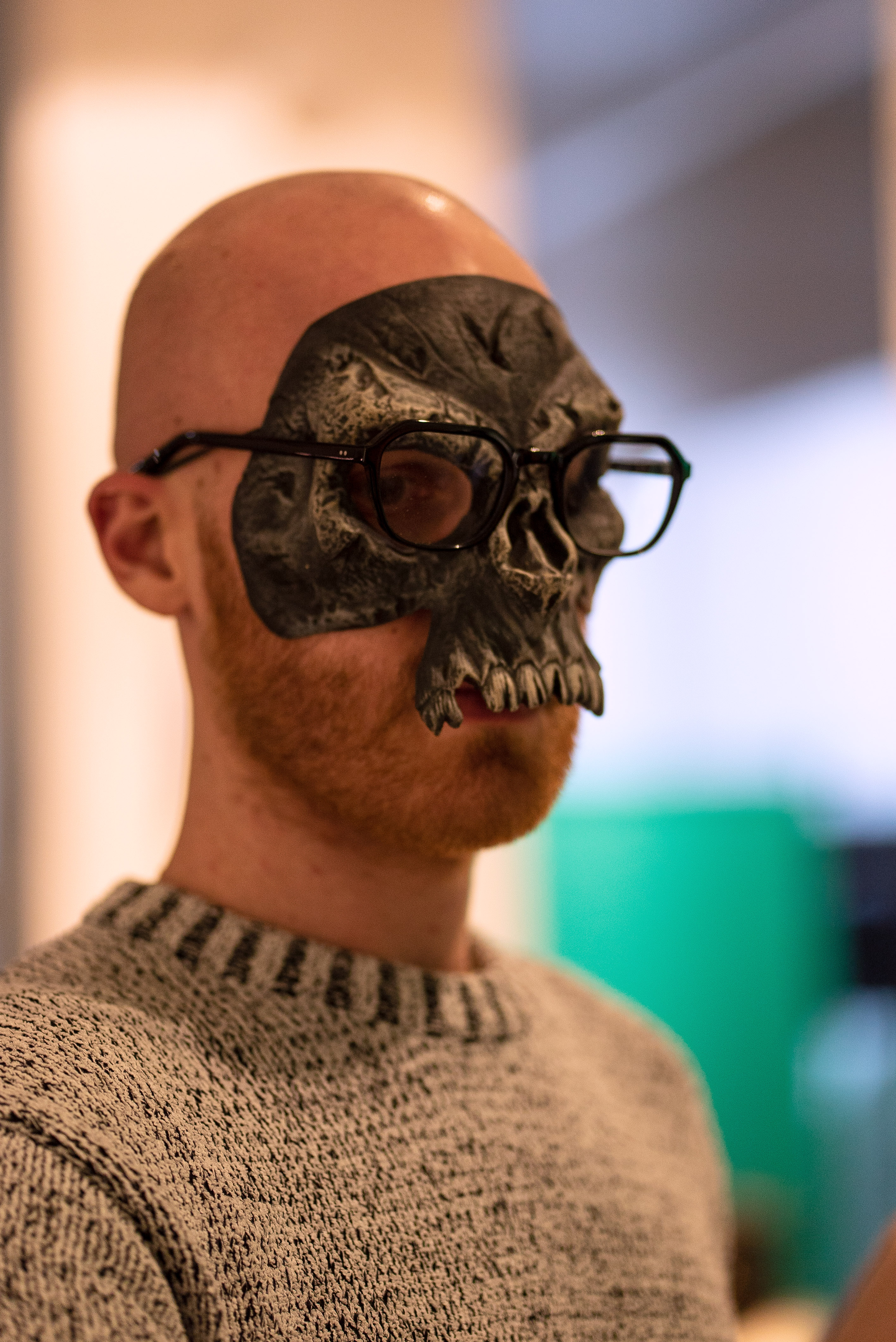 The photo is a close up shot of a person wearing a skull mask. On top of the skull mask they wear their glasses.