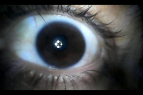 The video still shows a close-up of an eye that is staring directly into the camera. The pupil reflects light source.