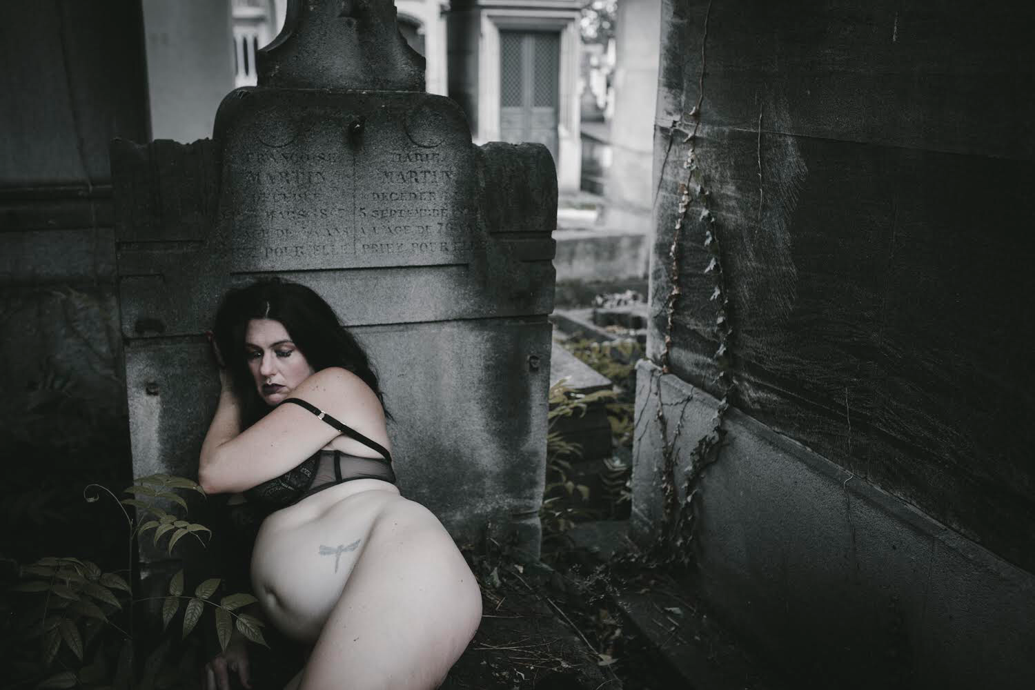 A slightly desaturated photograph of a pregnant person laying against an old, waterstained grey headstone in a cemetery. More cemetery scenery and some ivy on a wall are visible nearby. The person has long, dark hair and is wearing dark lipstick and makeup. They are wearing a black structured bra, and have a dragonfly tattoo on their side. Their eyes are closed, and they are slumped on their right side, with their left hand under their head and their left bra strap down on their arm. To the left of them, a fern grows.