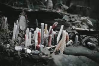A slightly desaturated close-up image of a rocky outcropping with many candles in reds, pastels, and whites, some textured and some not. Some of the the candles are burnt and wax has spread. Behind them, a small circular mirror in an ornate brass frame is visible, and small flat stones are arranged around the candles. A bone resembling a human femur is visible on the left side of the frame on a ceremonial plate, and natural green foliage is visible in the background.