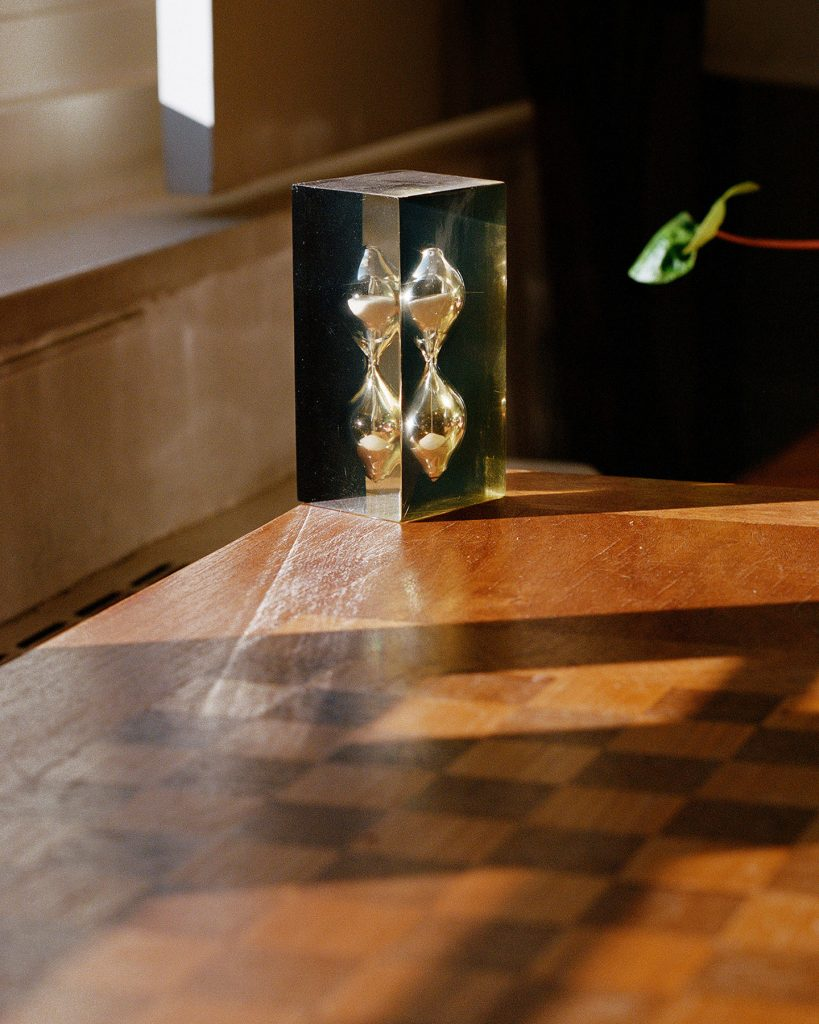 An image of a silvery hourglass-like shape in a translucent, square-shaped material. The object is sitting on a medium colored wooden table in sunlight. A checkered pattern is visible in the shadow on the table, and a plant's leaves are visible on the side of the frame next to the object.