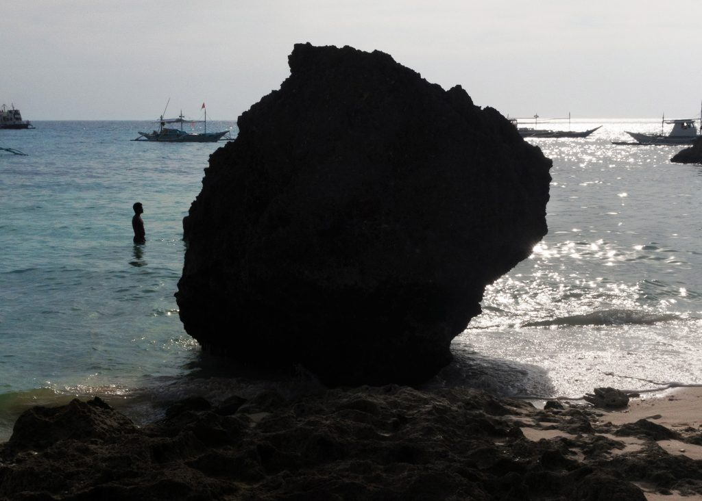 An image of a large, dark boulder sitting in shallow water on a tropical beach. A human and several votes are visible behind the shadowed boulder.