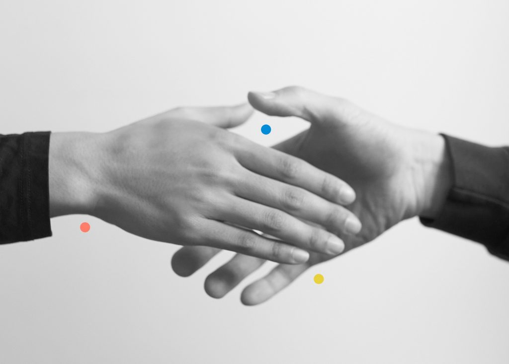 A black and white image of two hands about to touch or shake, presented symmetrically from the wrist down. A red dot is under the wrist, a yellow dot is under the pinky finger, and a blue dot is between the two thumbs in the frame.