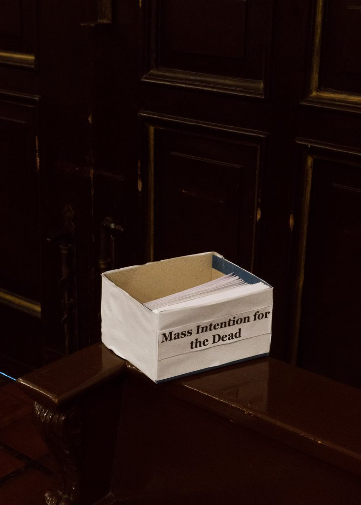 "A small paper box on a dark wooden table. The box has a label which reads ""Mass intention for the dead"". White pieces of paper are stacked neatly inside."