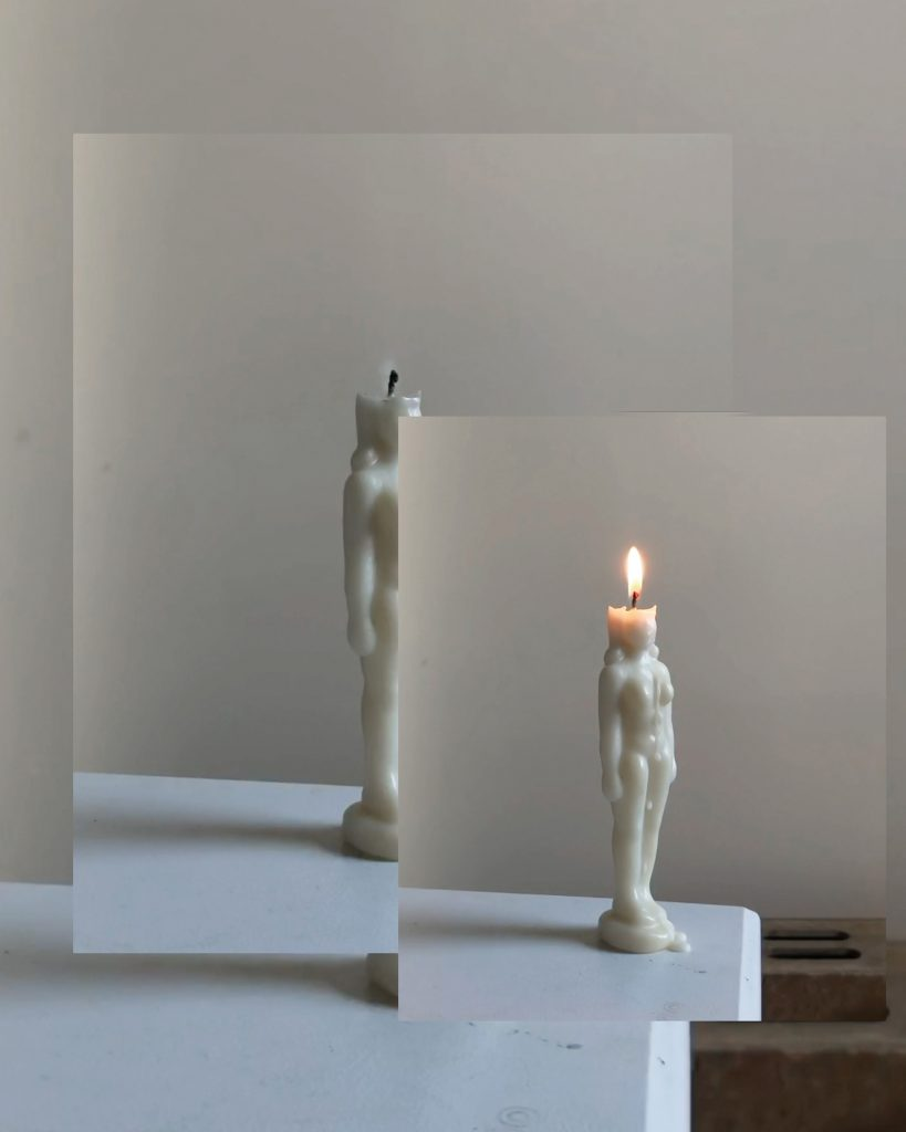 An image of a human-shaped candle with breasts on a table, superimposed over two images of the same scene. The background image is mostly obscured, while the middle image shows the candle put out. The top and smallest image shows the candle lit and dripping wax.