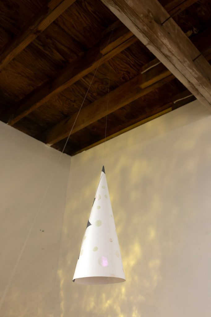 An image of a triangular paper hat suspended from the ceiling, in a room with dappled lighting across the walls. A wooden ceiling is visible above.