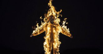 Image from a Cassils of a person on fire againsta a black background, presumably wearing a flame proof suit, arms outstretched.