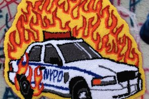 An image of a handmade rug depicting a NYPD cop car on fire with red and yellow flames. The rug is depicted on a graffitied stone wall.