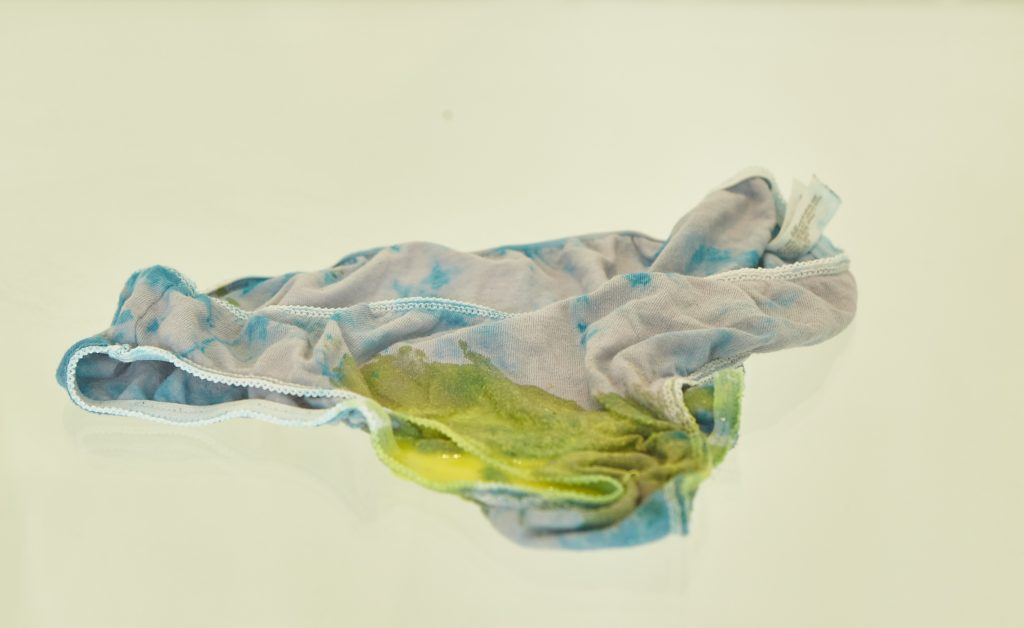 Tie-dyed underwear covered in yellow slime in a glass display case
