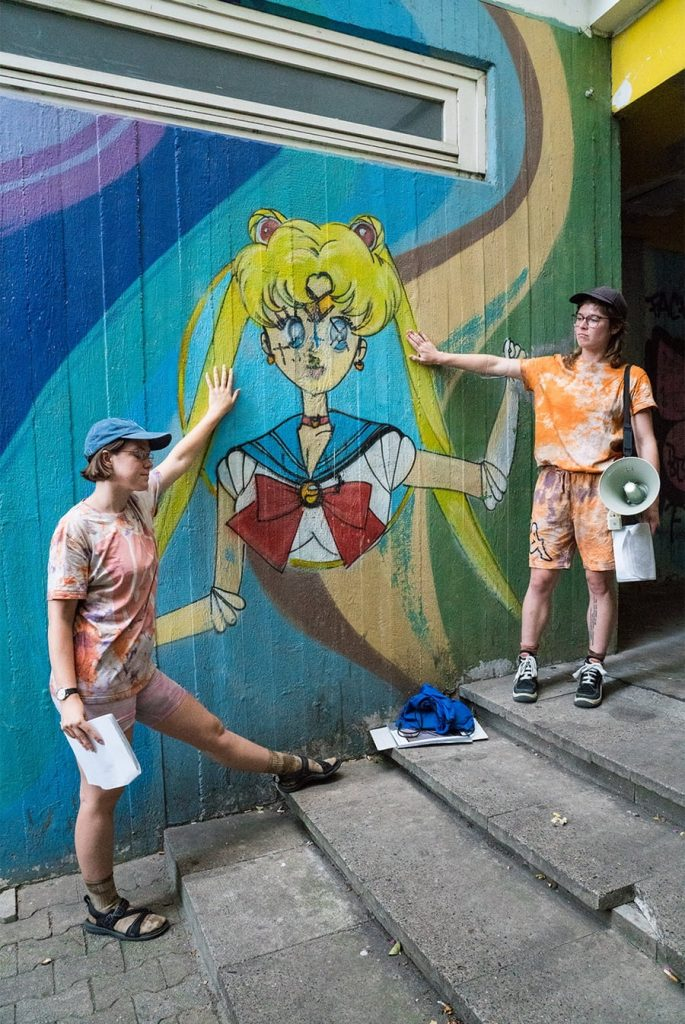 Frances and Louise lovingly put their hands on a mural of Sailor Moon with graffitied satanic symbols on her.