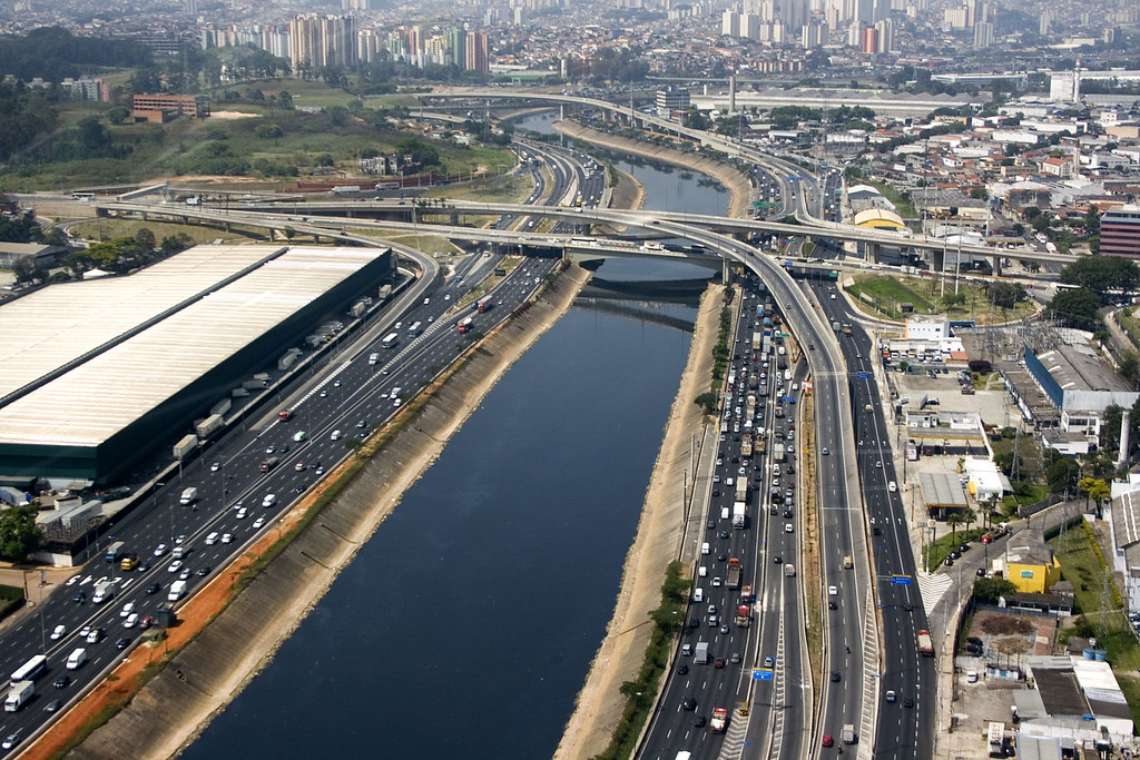 A bird's eye view of the river Tietê, São Paulo, with multi-lane highways on either side, many buildings and industry, and a bridge.