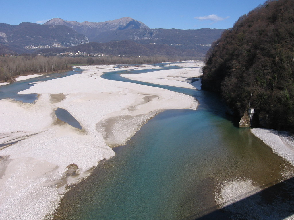 a birds eye view of Tagliamento river, Italy, a wide riverbed with lots of white sandy areas, mountains and houses in the distance, and trees lining its side.  The trees have no leaves and the sky is blue.